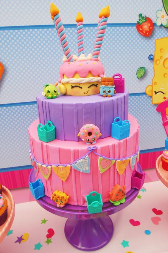 Three-tier birthday cake with Shopkins cake toppers.