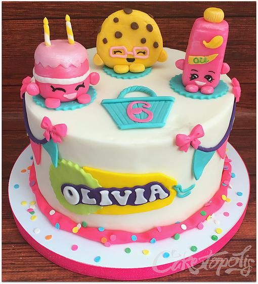 A pink and white Shopkins cake with sprinkles and character cake toppers.
