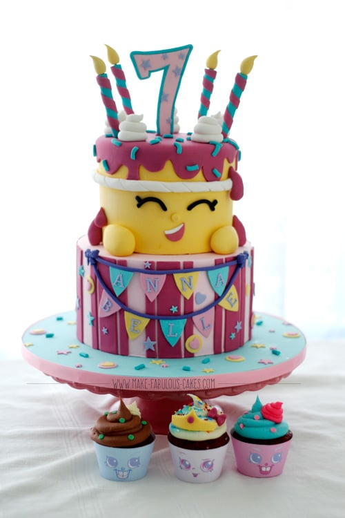 Two-tiered Shopkins inspired cake with cupckakes.