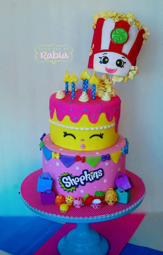 A two-tiered Shopkins-inspired cake with multi-colored banners.