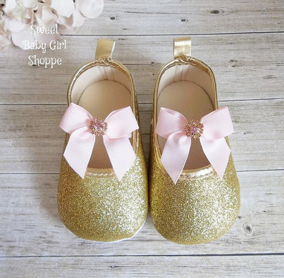 Glittery pink and gold baby shoes with pink bows.