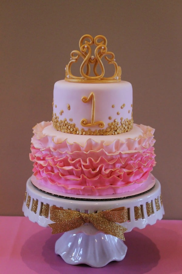 A pink and gold birthday cake with a crown topper.