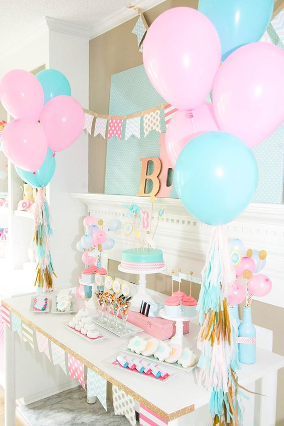 A pink and blue themed gender reveal dessert table.