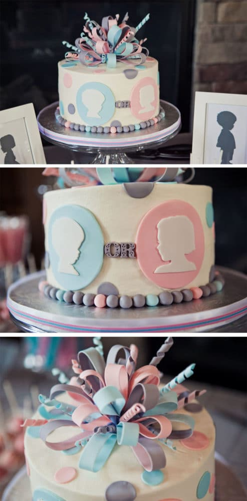 A gender reveal party cake in pastel colours with ribbons and confetti on top.