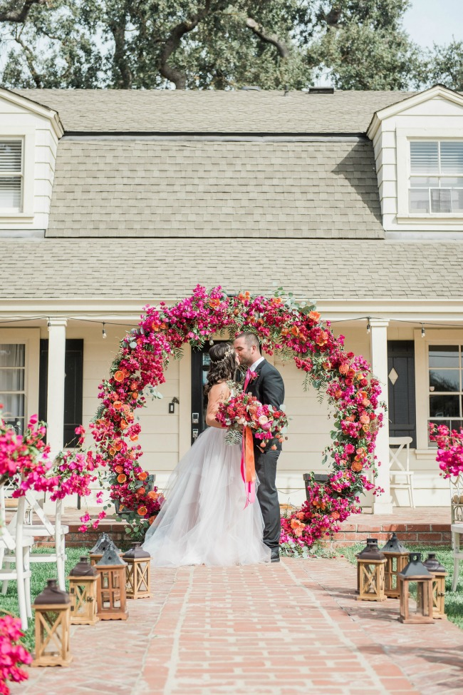 Gorgeous vibrant flowers on this giant circle ceremony wreath- wedding decoration ideas
