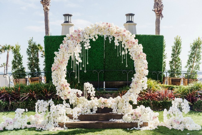White and pink circle ceremony arch with flowers